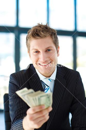 Junior businessman holding dollars and smiling at the camera