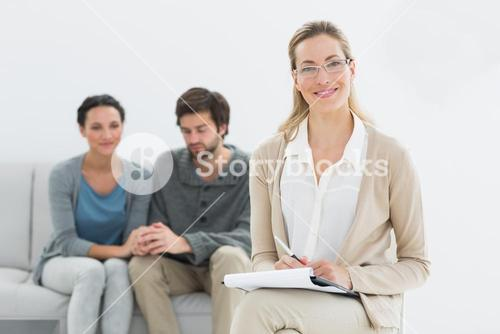 Female counselor with young couple in background