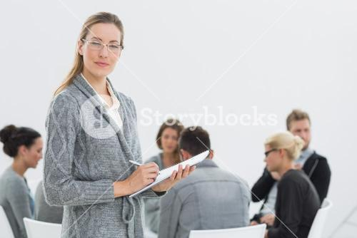 Therapist with group therapy in session in background