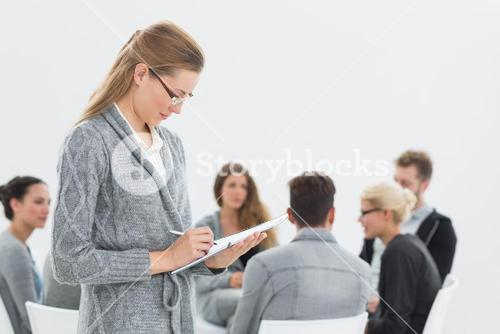 Therapist writing notes with group therapy in session