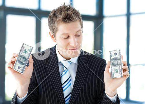 Young businessman holding dollars