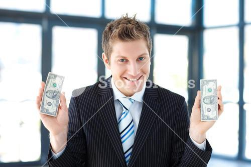 Young businessman holding money in office
