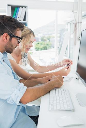 Smiling casual young couple working on computer