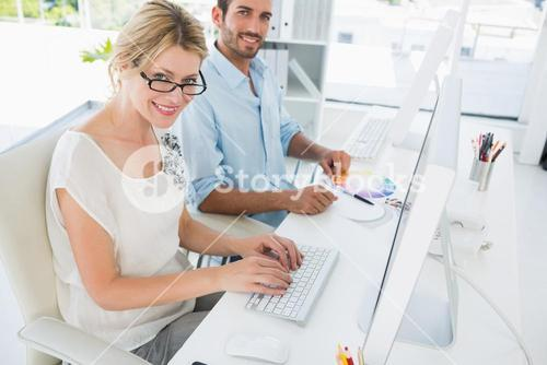 Casual young couple working on computers