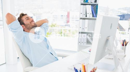 Casual man resting with hands behind head in office