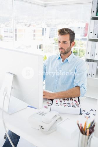 Concentrated male photo editor working on computer