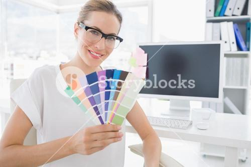 Female photo editor holding colors in office