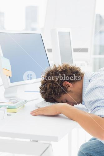 Casual businessman with head over keyboard at desk