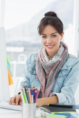 Smiling casual woman using computer in office