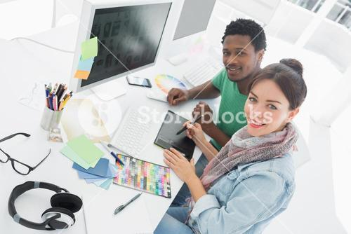 Artist with colleague drawing something on graphic tablet