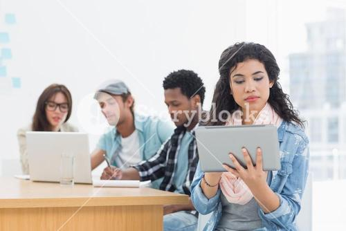 Concentrated woman using digital tablet with colleagues behind in office