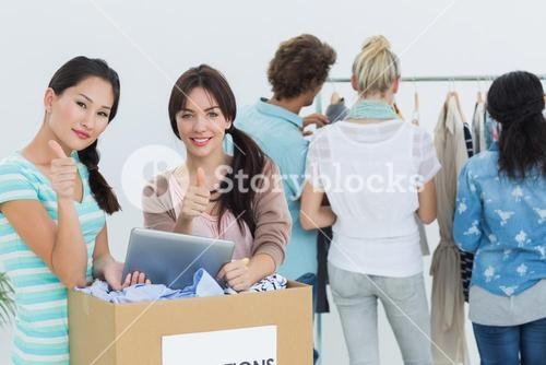 People with clothes donation and digital tablet gesturing thumbs up