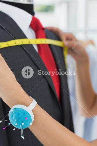 Hands measuring suit on dummy