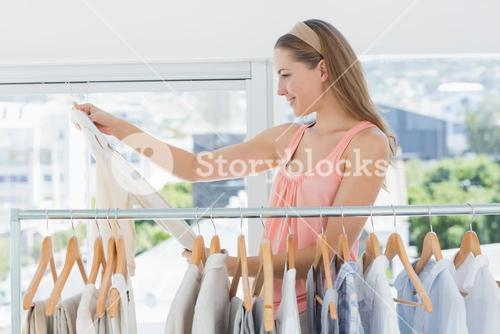 Female fashion designer looking at shirt by rack of clothes in store