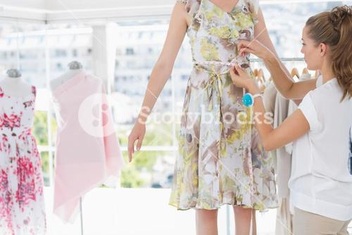 Fashion designer measuring models waist