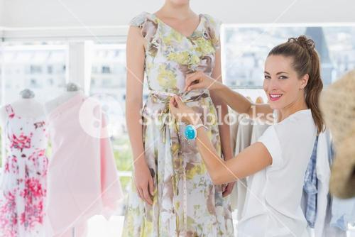Female fashion designer measuring models waist