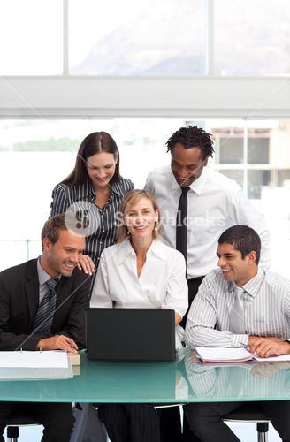 Female manager working with her team with a laptop in office