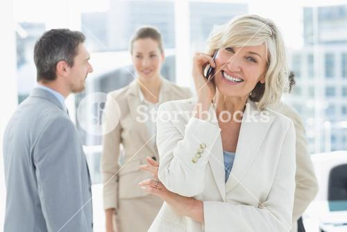 Mature businesswoman on call with colleagues at office