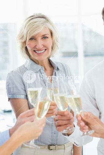 Businesswoman toasting with champagne in office