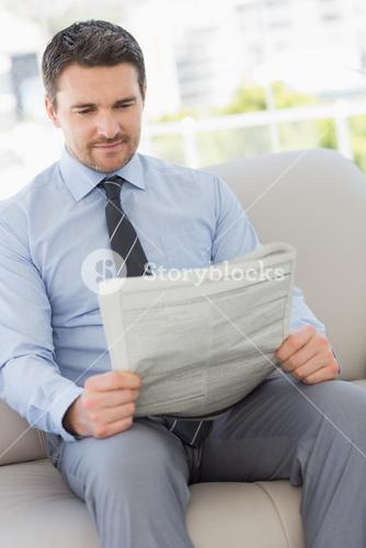 Well dressed young man reading newspaper at home