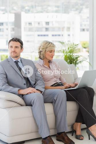 Well dressed man with woman using laptop at home