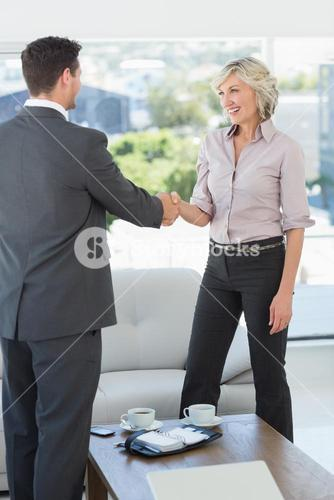 Executives shaking hands over a coffee table at home