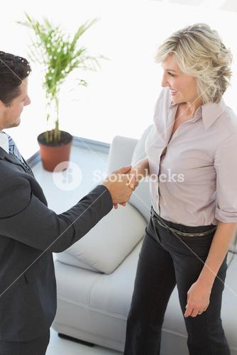 Executives shaking hands in the living room at home