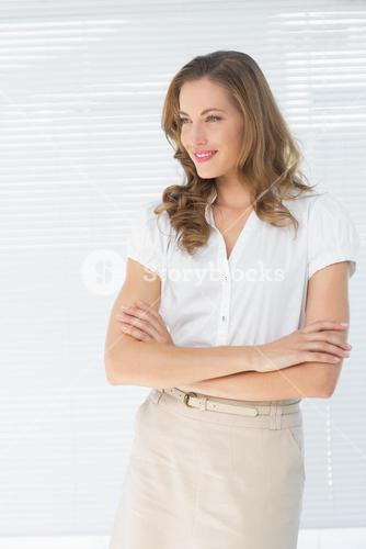 Businesswoman with arms crossed against blinds
