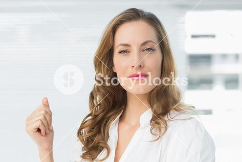 Smiling young businesswoman against blinds