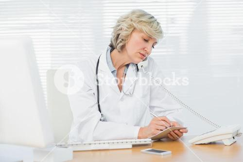 Female doctor using phone by computer at medical office