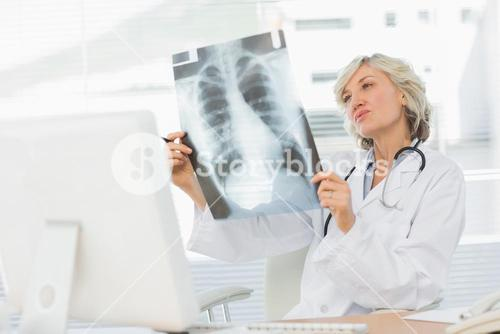 Female doctor examining xray in medical office