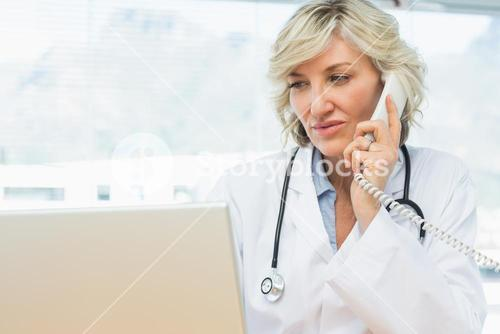 Doctor using laptop and phone in medical office
