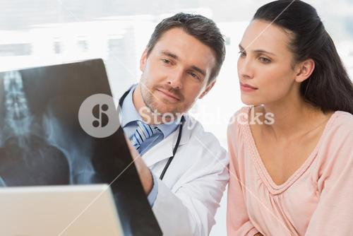 Male doctor explaining xray report to patient