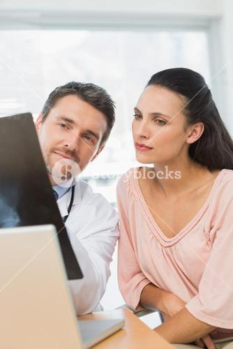 Male doctor explaining xray report to a patient