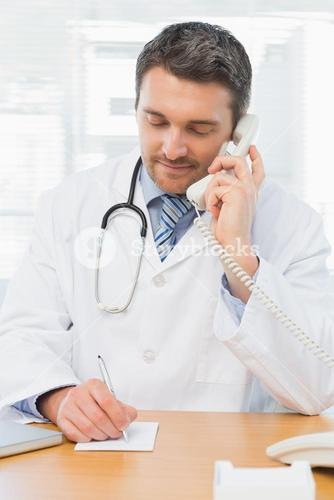 Concentrated doctor using phone while writing notes