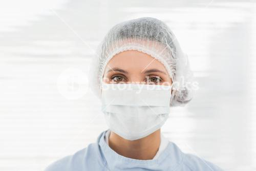 Female surgeon wearing surgical cap and mask