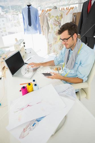Fashion designer using laptop and cellphone