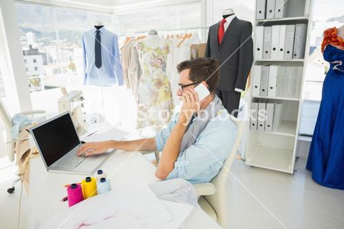 Male fashion designer using laptop and cellphone