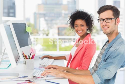Smiling casual young couple working on computers