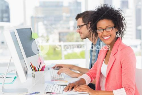Casual young couple working on computers in office