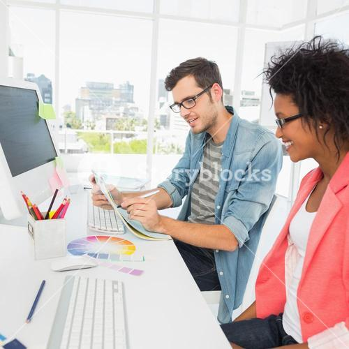 Casual young couple working on computer in office