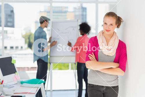 Casual artist with colleagues in background at office