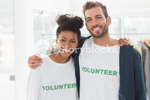 Portrait of two young volunteers with arms around