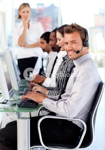 Smiling female leader managingher team in a call center
