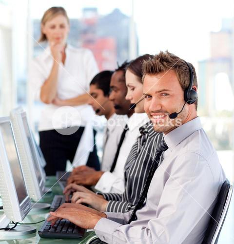 Happy female leader managingher team in a call center