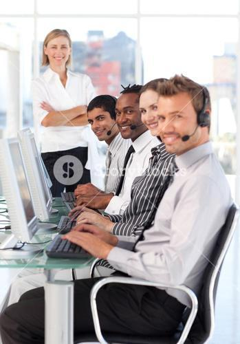 Serious female leader managingher team in a call center