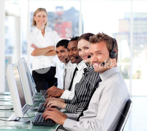 Cheerful female leader managingher team in a call center