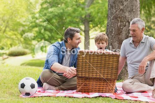 Grandfather father and son with picnic basket