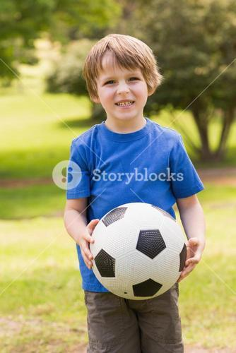 Smiling young boy holding ball in park