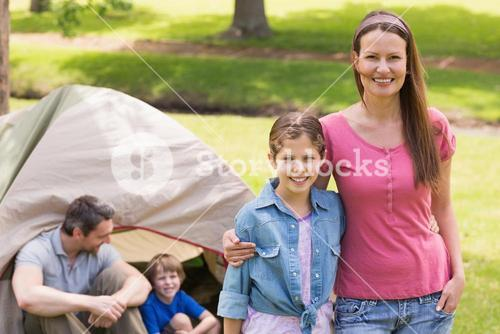 Mother and daughter with family behind in park